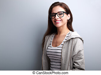 Beautiful young woman in casual wear with toothy smile on...