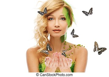 Beautiful young woman in conceptual spring costume with butterflies around her