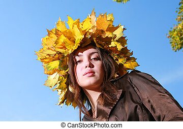 Beautiful young woman in crown of golden autumn leaves, blue sky behind.