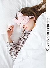 Beautiful young woman in cute sleep mask