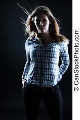 Beautiful young woman in dramatic light