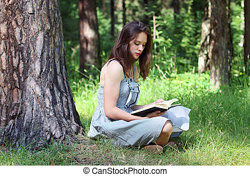 Beautiful young woman in dress sitting under tree on grass