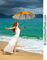 Beautiful young woman in dress standing on the beach with an umbrella before the rain against a background of dramatic clouds