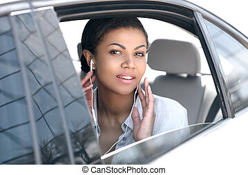 Beautiful young woman in earphones sitting in car and looking at camera
