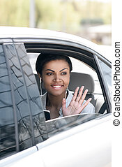 Beautiful young woman in earphones sitting in car and waving hand