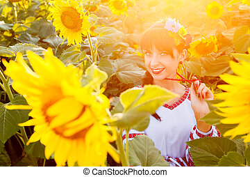 Beautiful young woman in embrodery on a sunflower field