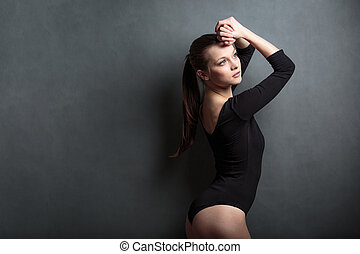 Beautiful, young woman in front of a grey background