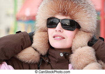 beautiful young woman in fur hat and sunglasses in winter, children's playground
