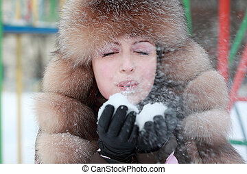 beautiful young woman in fur hat blowing snowflakes in winter, children's playground