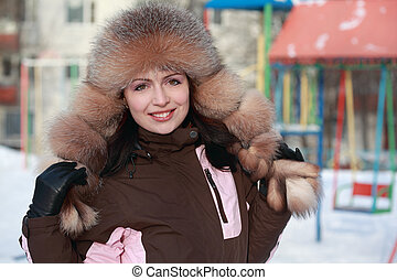 beautiful young woman in fur hat in winter, children's playground