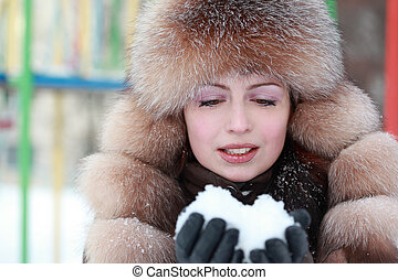 beautiful young woman in fur hat keeps snow in winter, children's playground