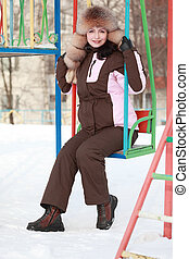 beautiful young woman in fur hat sits on swing in winter, children's playground
