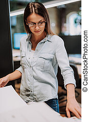 Beautiful young woman in glasses looking at blank sheets of paper