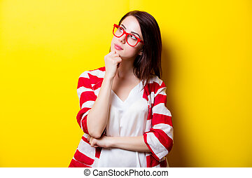 beautiful young woman in glasses standing in front of wonderful yellow background