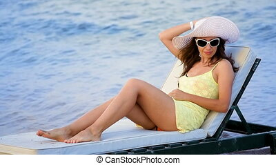 beautiful young woman in glasses sunbathing on the beach against the sea