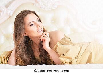 Beautiful young woman in golden dress