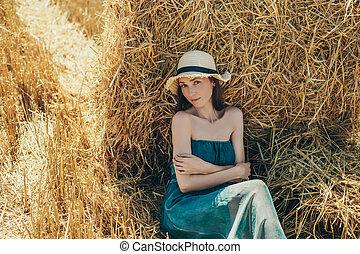 Beautiful young woman in green dress lies close-up