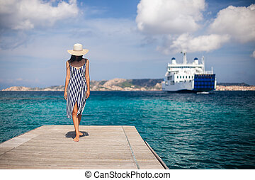 Beautiful young woman in hat walking on wooden pier on Sardinia beach