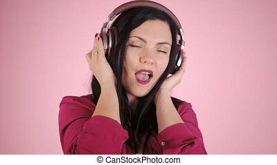 Beautiful young woman in headphones listening to music singing with closed eyes standing on a pink background in shirt. Slow motion