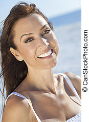 Outdoor portrait of a beautiful young brunette woman in her thirties taken at the beach with the sea behind her