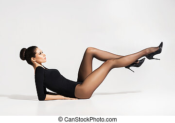 Beautiful, young woman in hosiery laying on the floor -...