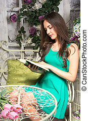 Beautiful young woman in interior garden with a book