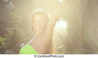 Beautiful young woman in jewelry in a bikini posing in the garden under spray of water at sunset