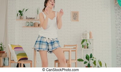 Beautiful young woman in kitchen dancing in the morning. Brunette girl wearing pajamas haves fun at home. Slow motion.