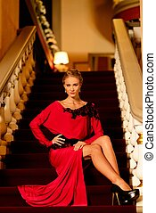 Beautiful young woman in long evening dress sitting on a steps in luxury interior