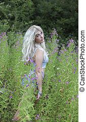 Beautiful young woman in long grass