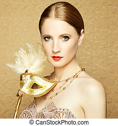 Beautiful young woman in mysterious golden Venetian mask