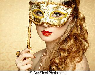 Beautiful young woman in mysterious golden Venetian mask....