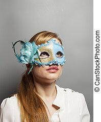 Beautiful young woman in mysterious venetian mask