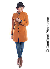 Beautiful young woman in orange coat posing on a white background.