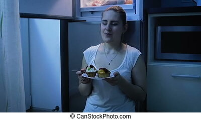 Beautiful young woman in pajamas eating on kitchen at night....