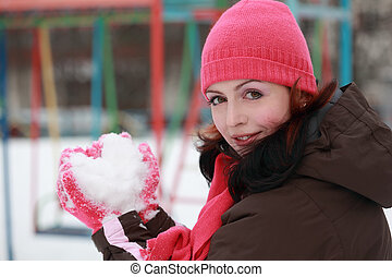 beautiful young woman in pink hat keep snow in winter, snow in form of heart, children's playground