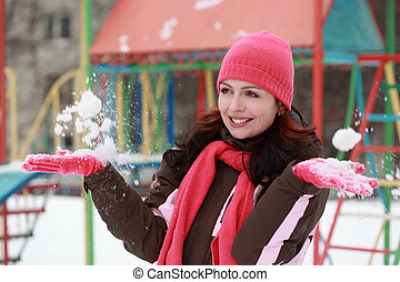 beautiful young woman in pink hat play with snow in winter, children's playground