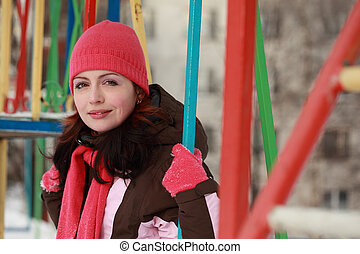 beautiful young woman in pink hat sitting on swing and smiling in winter, children's playground