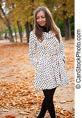 Beautiful young woman in polka dot trench at fall