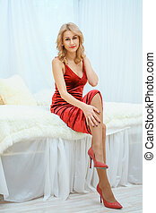 beautiful young woman in red dress lying sitting on bed.