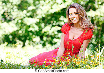 young woman in red dress sitting on grass