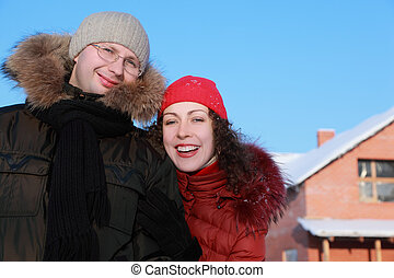 beautiful young woman in red jacket and man in glasses at winter outdoors, house