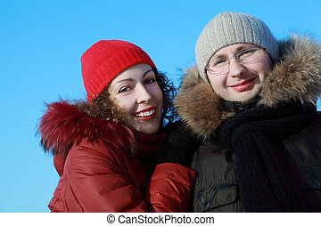 beautiful young woman in red jacket and man in glasses at winter outdoors