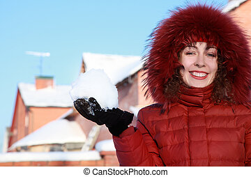 beautiful young woman in red jacket keeps snow and smiles at winter