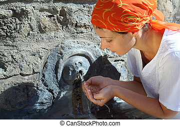 beautiful young woman in red kerchief drinking water from small fountain in Vatican walls