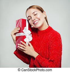 Beautiful young woman in red sweater. Girl with gift