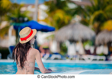 Beautiful young woman in red swimsuit relaxing in swimming pool. Happy girl in outdoor pool at luxury hotel