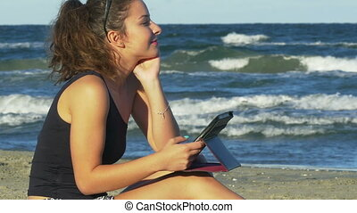 Beautiful young woman in romantic mood holding a tablet pc by the sea