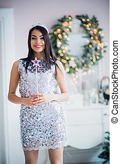 Beautiful young woman in Santa Claus clothes over Christmas background.