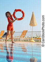 Beautiful young woman in shorts and T-shirt throws red buoy...